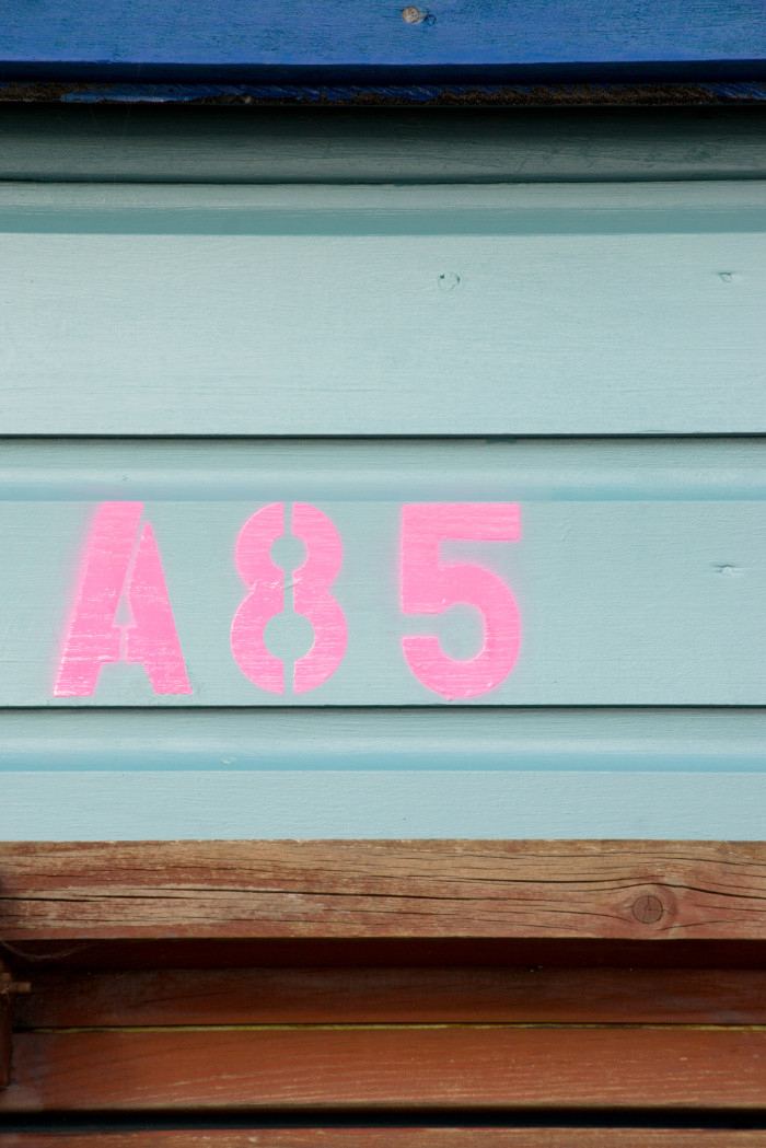 A blue and turquoise beach hut with a pink number painted on it