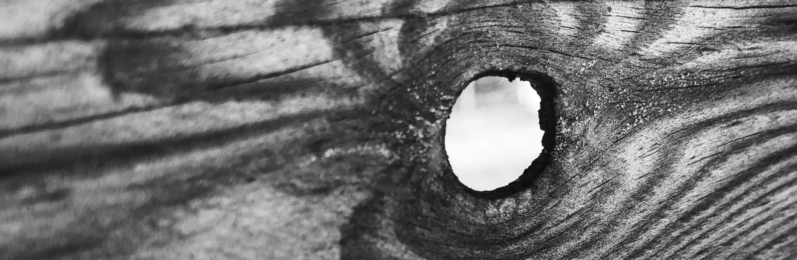 A black and white image of a knothole in pine woodgrain